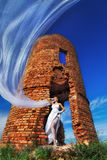 Bride with long veil. Staying against abandoned ruins in the evening Royalty Free Stock Image