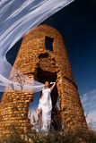Bride with long veil. Staying against abandoned ruins in the evening Stock Photography