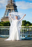 Bride with long veil near the Eiffel tower. Beautiful elegant bride with long veil near the Eiffel tower in Paris Royalty Free Stock Image