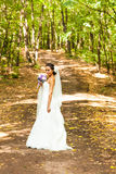 Bride with long veil. Bride posing in park Royalty Free Stock Image