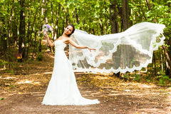 Bride with long veil. Bride posing in park Royalty Free Stock Images