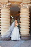 Bride with long veil. Standing near the column Royalty Free Stock Photos