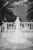 Bride with long veil and train. Bride in luxury wedding dress with long veil and train in black and white back view Royalty Free Stock Photos