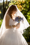Bride with long white veil looking at wedding bouquet Royalty Free Stock Photography