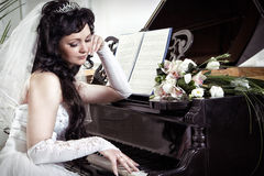 Bride longs at the piano. The bride looks thoughtfully at the piano stock photography