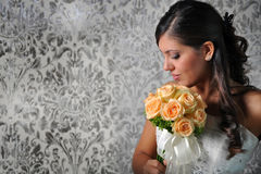 BRIDE LOOKING AT BOUQUET. A lovely bride looks down at her bouquet stock image