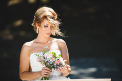 Bride Looking at Bouquet. Bride looking at wedding bouquet in wind Royalty Free Stock Photos
