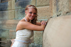 Bride looking at the camera with arms crossed. A Bride leans against a sandstone building and smiles Royalty Free Stock Image