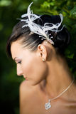 Bride looking down. With feathers in her hair Stock Photo