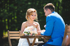 Bride Looking at Groom`s Hands. At table with bouquet Royalty Free Stock Photos