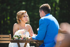 Bride Looking at Groom. At table in sunlight Royalty Free Stock Photo