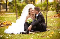 Bride looking at grooms eyes while sitting on grass at park Stock Photography