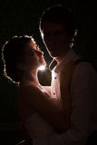 Bride looking at her husband with a light behind Stock Image