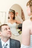 Bride looking at mirror and groom sitting near Stock Photo