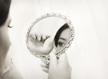 Bride looking in the mirror, vintage style royalty free stock photography