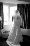 Bride looking out of window. Rear view of bride in traditional white wedding dress and veil looking out of hotel bedroom window Royalty Free Stock Images