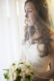 Bride looking outdoors. Picture of a bride dressed in her white gown, holding her flower bouquet and looking through a window Royalty Free Stock Images