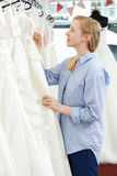 Bride Looking At Price Tag On Wedding Dress In Bridal Boutique. Bride Looking At Price Tag On Wedding Dress Stock Photography