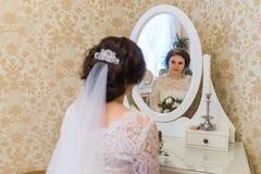Bride looking at vintage mirror Royalty Free Stock Images