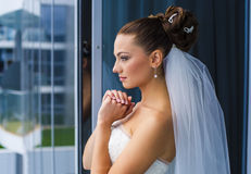 Bride are looking through the window. Royalty Free Stock Photography