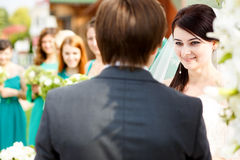 Bride looks charmed listening to the groom's oath.  royalty free stock photos