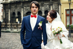 Bride looks at a confident groom in blue suit Royalty Free Stock Image