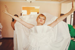 Bride looks funny putting on a wedding dress Stock Photos
