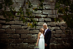 Bride looks in groom's eyes while they stand behind an old stone. Wall royalty free stock image