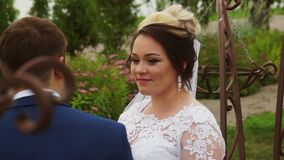 The bride looks at the groom. Sitting on a bench against the trees stock footage