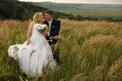 Bride looks happy leaning to a groom on the field.  royalty free stock images