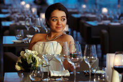 Bride looks happy sitting in an empty restaurant.  royalty free stock photography