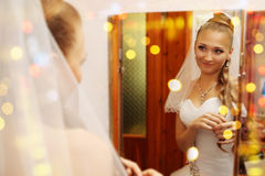 Bride looks in the mirror Stock Image