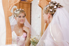 Bride looks in the mirror Royalty Free Stock Image