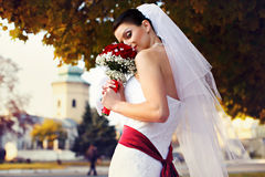Bride looks misterious holding a wedding bouquet Royalty Free Stock Photos