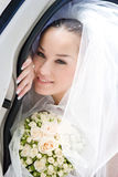 Bride looks out from the open door of the car Stock Photo