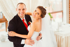 Bride looks over her shoulder in the hugs of groom. Bride looks over her shoulder while standing in the hugs of handsome groom royalty free stock image