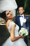 Bride looks over her shoulder and smiles while groom waits on th Stock Image