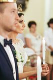 Bride looks seriously holding a candle in her arms during the ce. Remony royalty free stock photos