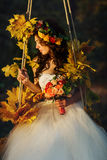 Bride looks stunning sitting on the swing full of autumn flowers Royalty Free Stock Photo