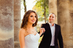 Bride looks up in the air while groom holds her fingers tenderly Royalty Free Stock Images