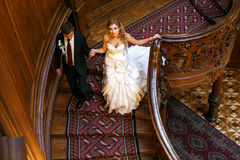 Bride looks up while she goes downstairs with a groom Stock Image
