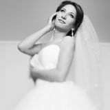 Bride looks up in the sky while holding her face with an arm Royalty Free Stock Images