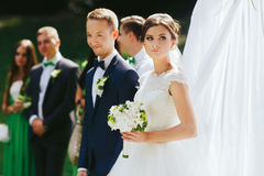 Bride looks up in the sky standing with groom behind an altar Royalty Free Stock Images