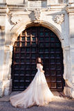 Bride in luxurious dess stands before the huge steel gates.  royalty free stock photos