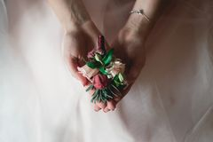 Bride in a luxurious wedding dress holding a wedding buttonhole made of roses stock photos