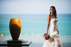 Bride in a luxurious white dress posing against the ocean stock photography