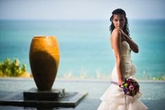 Bride in a luxurious white dress posing against the sea royalty free stock photos