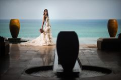 Bride in a luxurious white dress stands on the background of the ocean in the middle of the jugs stock photos
