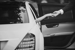 Bride in Luxury Car Gives Hand to Bridegroom royalty free stock images