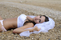 Bride lying  on the beach Stock Photo